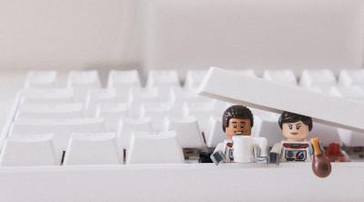 Dois bonecos de lego saindo do teclado, forma divertida de falar sobre modificação de CMS ou edição de sites